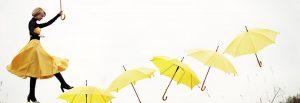 Eine Frau in einem gelben Rock mit einem gelben Regenschirm in der Hand. Sie läuft quasi in der Luft über 6 weitere gelbe Regenschirme.